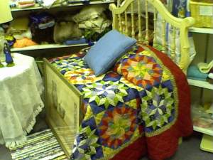 Using a for-sale head board, a packing box, and a for-sale bedspread in a thrift, consignment or resale shop